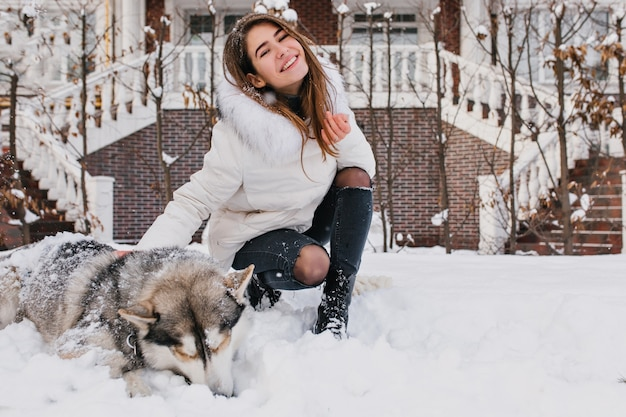 Joyful happy young woman having fun with cute husky dog in snow on street. cheerful mood, winter snowing time, lovely home pets, real friendship.