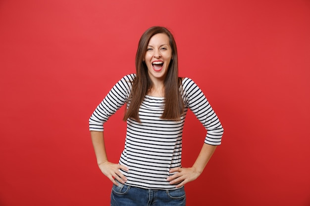 Joyful happy young woman in striped clothes keeping mouth wide open, standing with arms akimbo