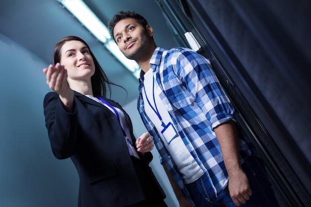 Радостная, услужливая милая женщина, стоящая со своим коллегой и показывающая ему направление, стоя в серверной