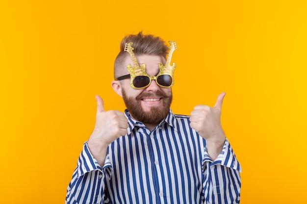 Радостный хипстерский мужчина поднимает пальцы вверх, позирует у желтой стены