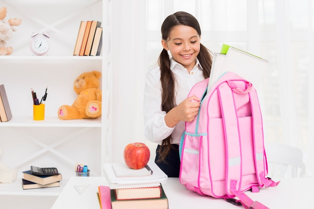 Joyful hispanic schoolgirl packing schoolbag