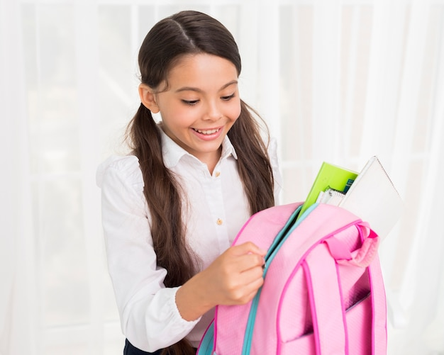 Joyful hispanic schoolgirl zipping up school bag