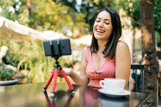 携帯電話で彼女のvlogのビデオを録画するうれしそうなヒスパニック系女性