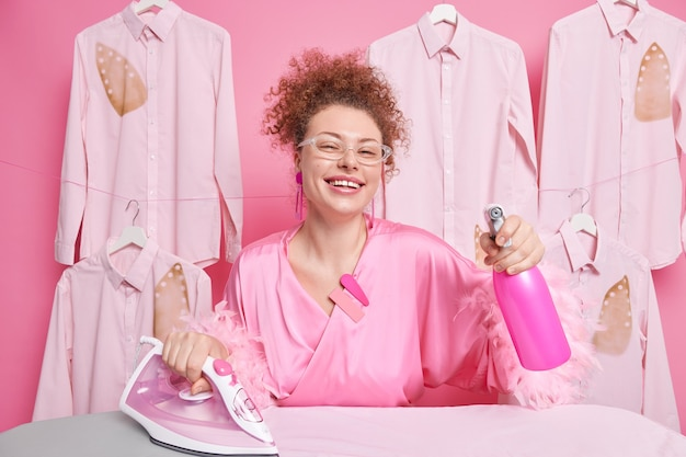 Joyful housewife spends all day on cleaning and ironing uses water spray bottle electric iron wears transparent glasses and dressing gown being at home poses near ironed clothes. housekeeping