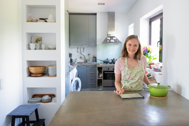 Joyful housewife writing notes on pad for recipe while cooking in her kitchen, using tablet near big saucepan on counter, looking at camera. front view. cooking at home and online cookbook concept