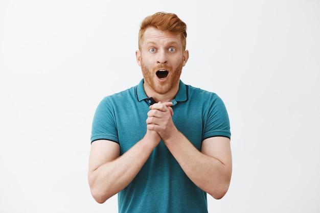 Радостный, впечатленный и возбужденный симпатичный мужчина-модель с рыжими волосами и щетиной, отвисшая челюсть и задыхающийся, сжимая ладони на груди и взволнованно глядя на что-то удивленное и удивительное