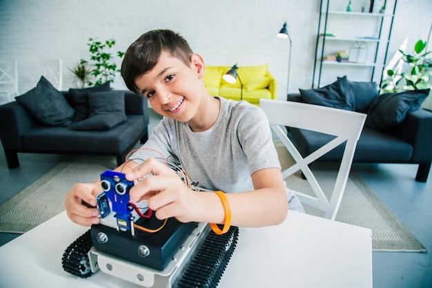 집에서 공학을 공부하면서 로봇 기술을 실험하는 즐거운 독창적인 남학생
