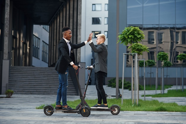 Joyful international office workers riding on electric scooters and give high fives at motion.