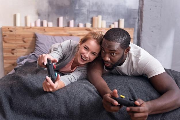 Радостная международная молодая пара играет в видеоигры, лежа в постели и весело.