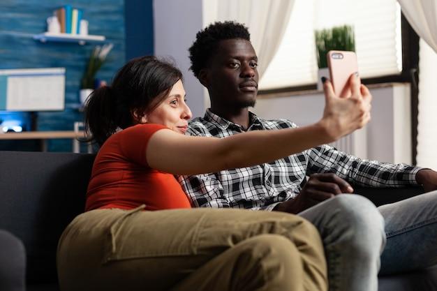 Радостная межрасовая пара, делающая селфи вместе дома. люди смешанной расы веселятся с фотографиями и снимками с помощью современного смартфона. многонациональные партнеры с цифровым устройством
