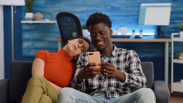 Радостная межрасовая пара, делающая селфи со смартфоном