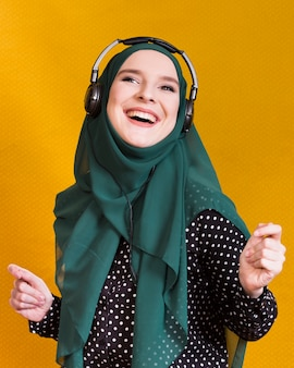Joyful islamic woman enjoying music on yellow backdrop