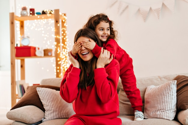 Joyful kid in red attire playing with mother. brunette woman spending weekend at home with daughter.