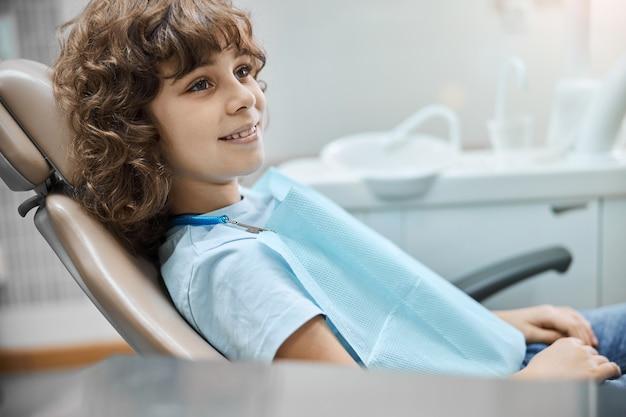 치과 약속 중에 치과 의자에 앉아있는 동안 곱슬 머리가 웃는 즐거운 아이