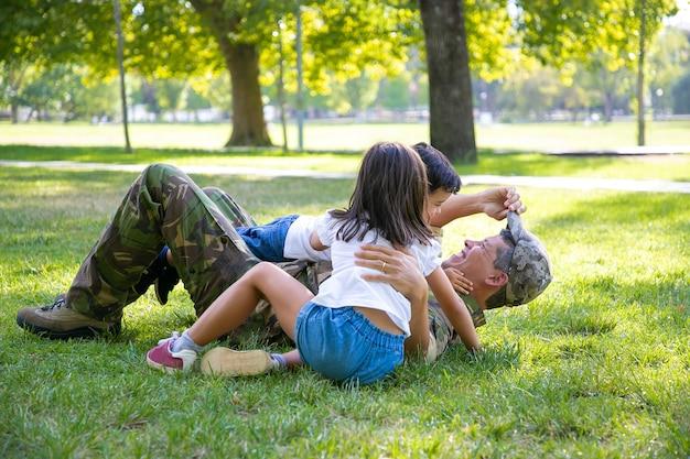 즐거운 아이들과 그들의 아빠가 거짓말을하고 공원에서 잔디에 놀고 있습니다. 선교 여행 후 아이들과 함께하는 행복한 군사 아버지. 가족 상봉 또는 귀국 개념