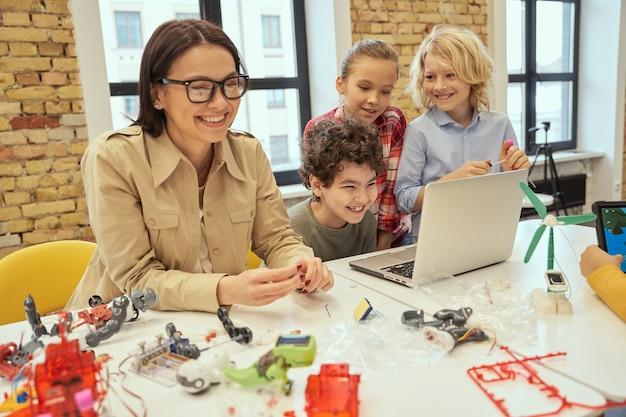 Веселые дети смеются вместе со своей молодой учительницей, изучая, как собрать робота