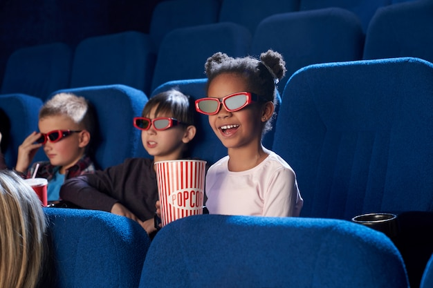 Joyful kids watching movie in 3d glasses, in cinema.