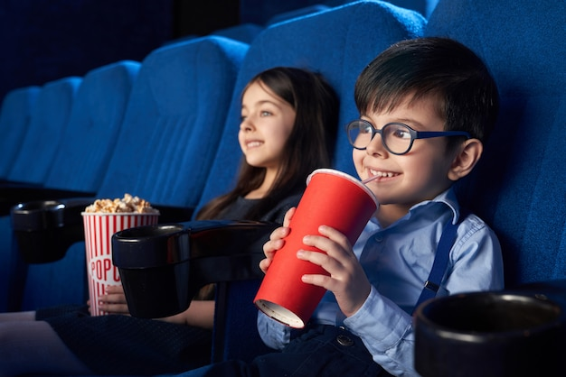 Joyful kids watching movie, drinking fizzy drink in cinema.