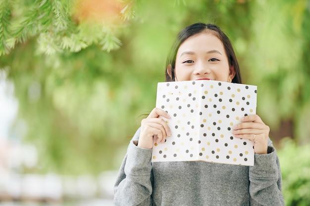 本で顔を覆ううれしそうな韓国の10代の少女