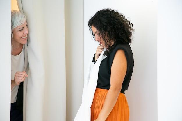 Радостные дамы вместе делают покупки в модном магазине, примеряют и обсуждают платья в примерочной. вид сбоку. потребительство или концепция покупок