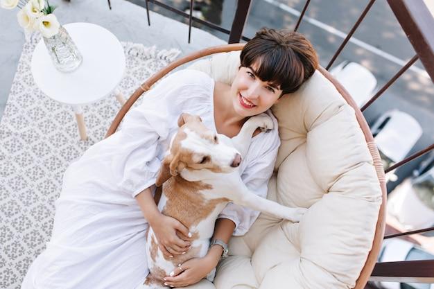 Signora allegra in accappatoio con acconciatura corta in posa sulla sedia con cane seduto vicino a vaso con fiori.