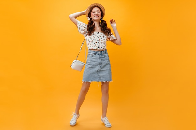Joyful lady dressed in denim skirt and cropped top posing with white bag on orange background.
