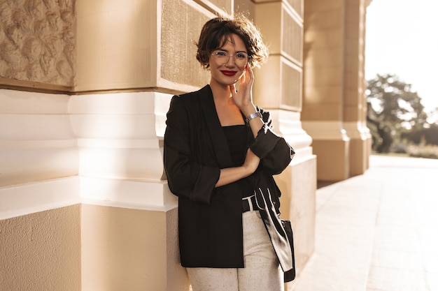 Joyful lady in jacket and white pants smiling outside. lovely woman with bright lips in eyeglasses outdoors.