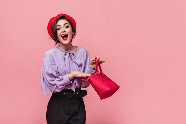 Joyful lady in red hat laughs, holding small bag in her hands on pink background.