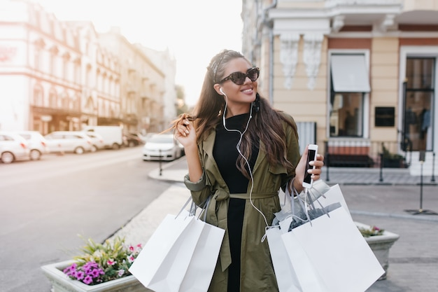 Signora allegra in occhiali da sole alla moda trascorrere del tempo in città a comprare vestiti nuovi