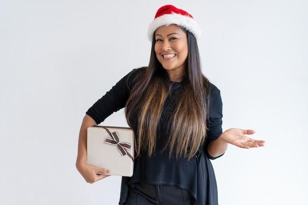 Joyful lady with christmas gift presenting news