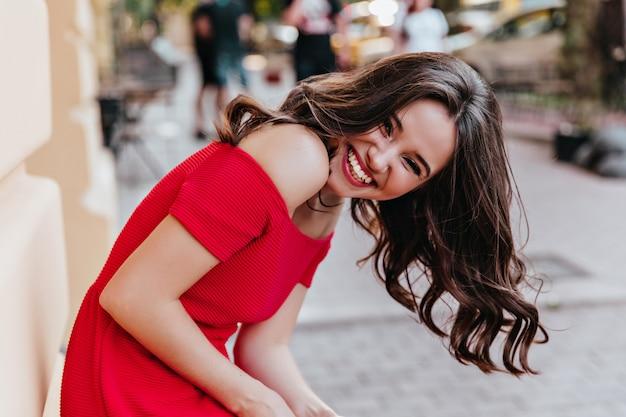都会の幸せを表現するエレガントな髪型のうれしそうな女性。路上で笑っている赤い服を着た官能的なブルネットの女性モデル。