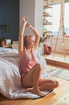 팔을 들고 즐거운 여성이 바닥에 헤드폰을 끼고 음악을 듣습니다.