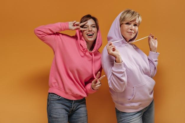 Радостная дама с короткими волосами в розовом наряде показывает знак мира, подмигивает и целуется с белокурой старухой на оранжевом фоне.