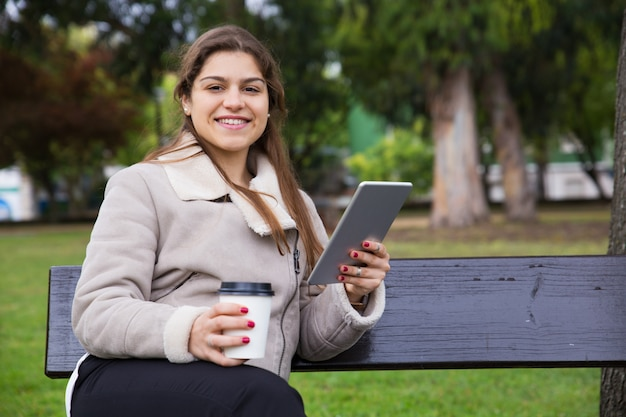 Joyful latin college girl with tablet drinking takeaway coffee