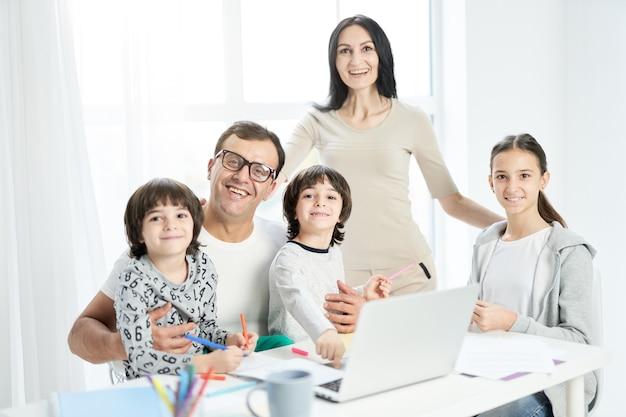 집에서 함께 시간을 보내는 동안 카메라를 보고 웃는 아이들과 함께 즐거운 라틴 가족. 아버지는 집에서 일하고 노트북을 사용하고 아이들을 지켜보고 있습니다. 기술, 가족 개념