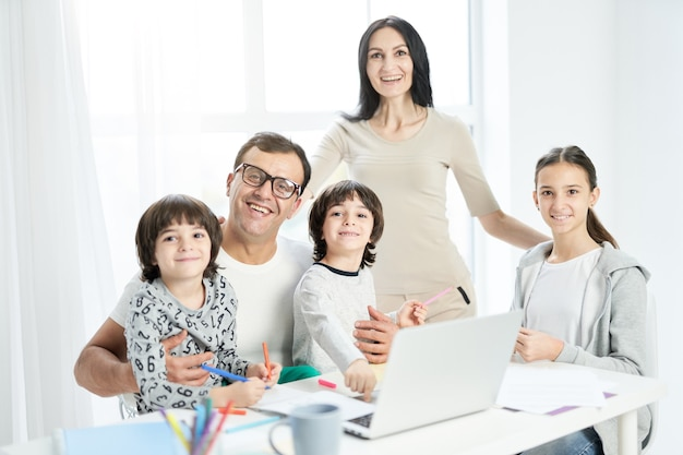 Joyful latin family with children smiling at camera while spending time together at home. father working from home, using laptop and watching kids. technology, family concept