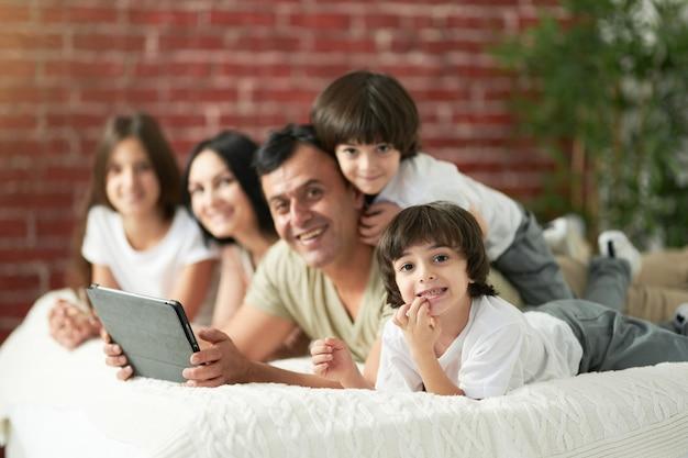 귀여운 어린 아이들과 함께 즐거운 라틴 가족이 집에서 함께 시간을 보냅니다. 사랑하는 아버지는 침대에 누워 아이들과 함께 만화를 보고 있습니다. 행복한 어린 시절 개념
