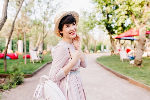 Joyful laughing girl in cute straw hat walking in park in sunny morning, enjoying good weather