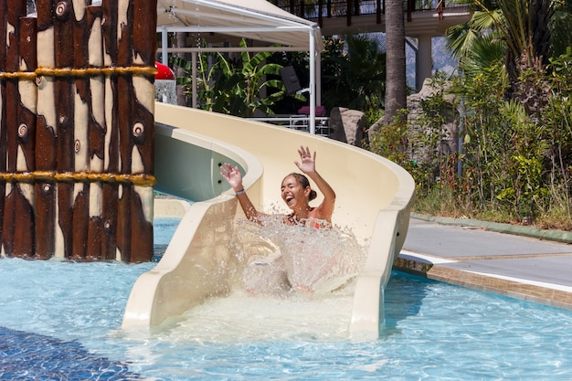 Joyful laughing teen girl goes down by water slide in the hotel aquapark