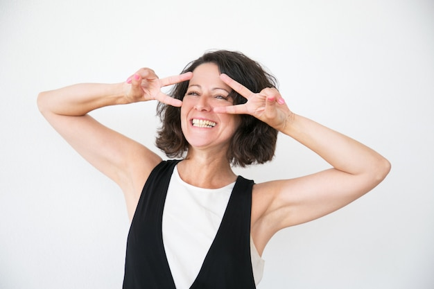 Joyful laughing woman in casual making peace gesture