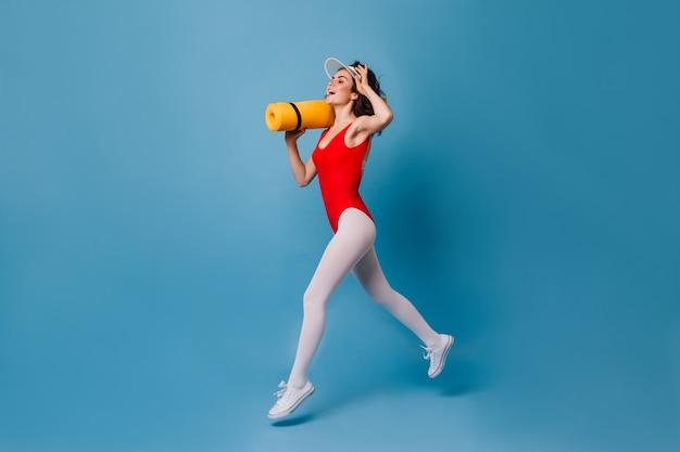 Joyful leggy brunette runs on blue wall