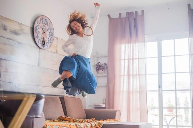 女性のための楽しいライフスタイルと成功のコンセプト-幸せのためにソファにジャンプする女性-陽気なポジティブな若い白人女性はジャンプで新しい生活を楽しんでいます