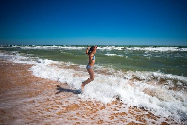 햇살 따뜻한 여름날에 폭풍우 치는 바다의 파도에 점프 즐거운 활동적인 소녀