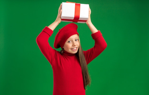 コピースペースで緑の壁に分離されたカメラを見て頭の上にギフトパッケージを保持している赤いベレー帽を身に着けているうれしそうな小さなブロンドの女の子