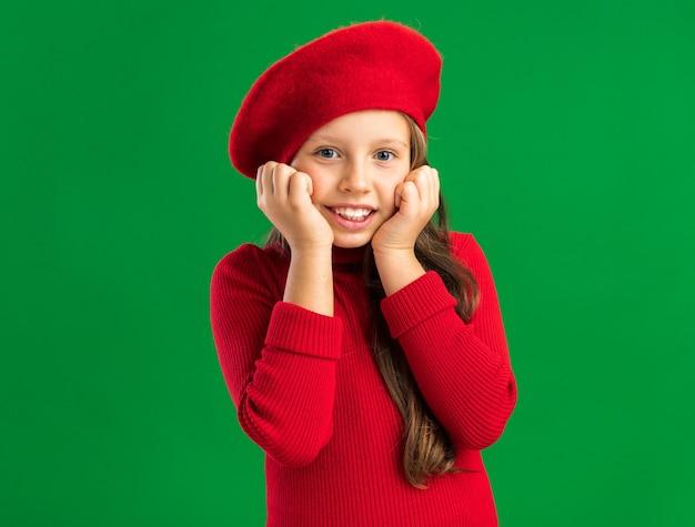 Радостная маленькая блондинка в красном берете, держась за подбородок, изолированную на зеленой стене с копией пространства