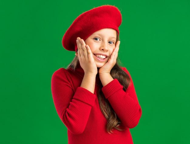 コピースペースで緑の壁に隔離された顔に手を保つ赤いベレー帽を身に着けているうれしそうな小さなブロンドの女の子
