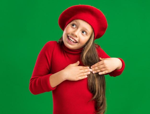 コピースペースで緑の壁に隔離された側を見て心に手を保つ赤いベレー帽を身に着けているうれしそうな小さなブロンドの女の子