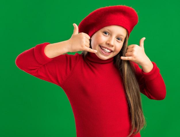 緑の壁に隔離されたカメラを見て親指を立て続ける赤いベレー帽を身に着けているうれしそうな小さなブロンドの女の子