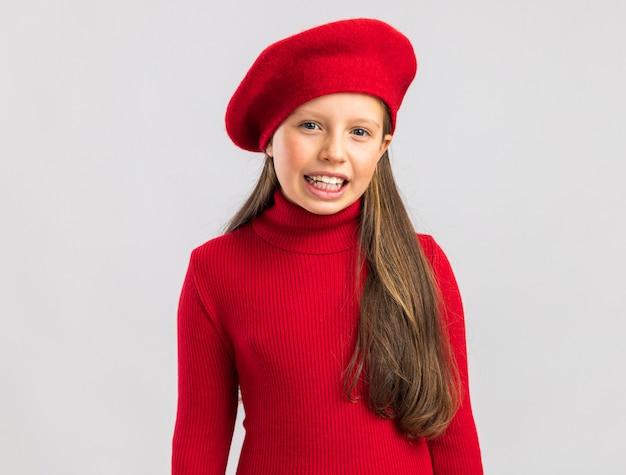 Gioiosa bambina bionda che indossa un berretto rosso che guarda la macchina fotografica e sorride isolata sul muro bianco con spazio per le copie