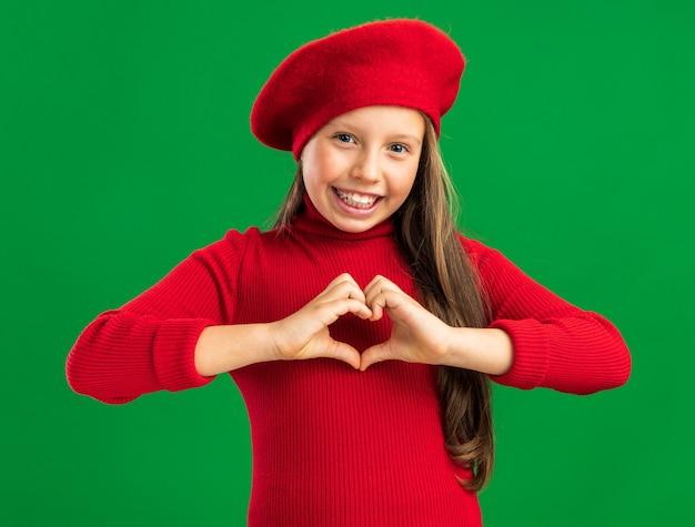 빨간 베레모를 쓴 즐거운 금발 소녀가 복사공간이 있는 녹색 벽에 격리된 앞을 바라보는 사랑의 제스처를 보여줍니다.